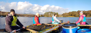 Malaysian family enjoying canoeing on coniston water with snowy mountains